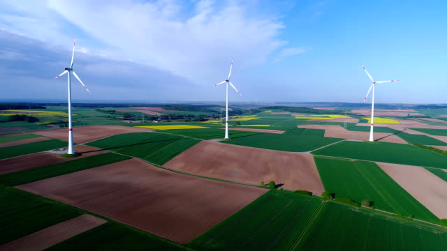 air panoramas of agricultural fields and wind generators producing electricity. alternative energy, three wind turbines in a green field - energia sostenibile video stock e b–roll