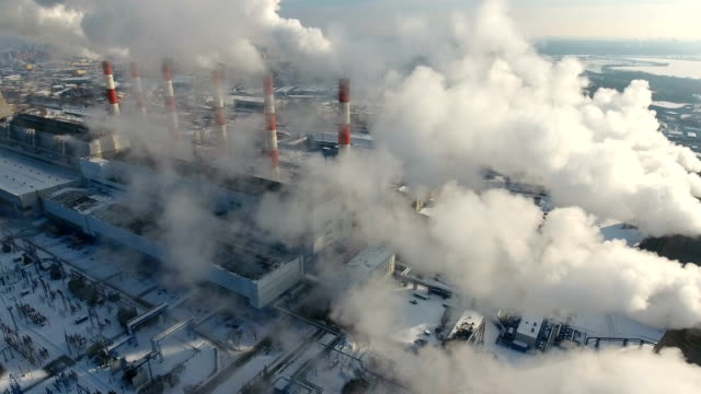 air pollution concept. power plant with smoke from chimneys. drone shot. - смог над городом стоковые видео и кадры b-roll