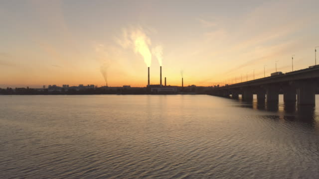 Air pollution, ecology. 4k aerial smoking plant at golden sunset. River.