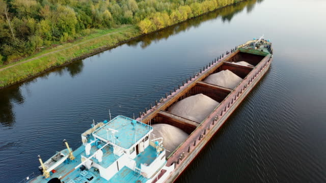 air view of the movement of the barge on the shipping channel in the area of locks and construction of the bridge - chiatta video stock e b–roll