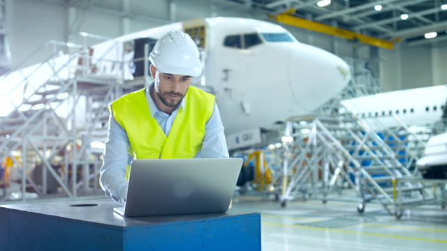 Aircraft Development Engineer wearing Safety Vest and Hardhat Uses Laptop and Blueprints to Analyze, Inspect and Work on Airplane Design in Airplane Design Facility