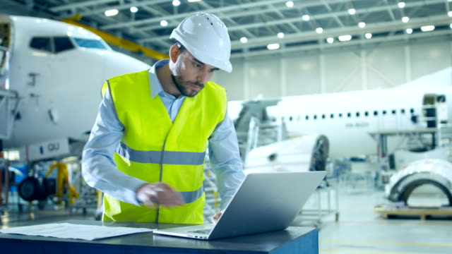 안전 조끼 및 hardhat을 착용 하는 항공기 개발 엔지니어는 비행기 설계 시설에서 비행기 디자인을 분석, 검사 및 작업 하기 위해 노트북과 청사진을 사용 합니다. - 항공 비행체 스톡 비디오 및 b-롤 화면