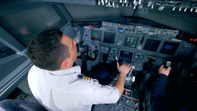 Aircraft flying process performed by two men in a cockpit