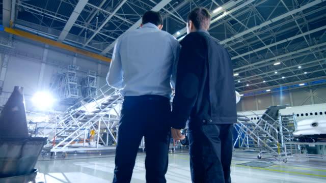 항공기 정비 정비사와 수석 엔지니어가 논의 하 고, 큰 비행기 개발 시설에 서 있는 동안 청사진을 참조 하십시오. 그들은 비행기를 분석, 검사, 개발 및 설계 합니다. - 항공 비행체 스톡 비디오 및 b-롤 화면