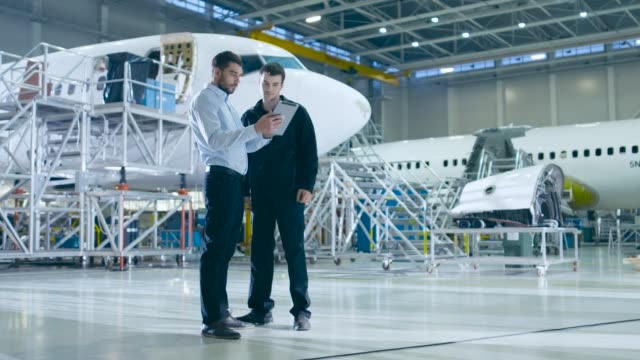 Aircraft Maintenance Mechanic and Chief Engineer Have Discussion, Consult Digital Tablet Computer While Standing in a Big Airplane Development Facility. They Inspect, Develop and Design Airplanes