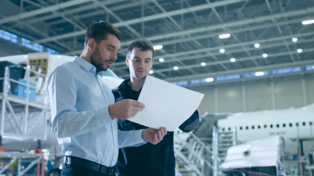 Aircraft Maintenance Mechanic and Chief Engineer Have Discussion, Consult Blueprints While Standing in a Big Airplane Development Facility. They Analyze, Inspect, Develop and Design Airplanes Aircraft Maintenance Mechanic and Chief Engineer Have Discussion, Consult Blueprints While Standing in a Big Airplane Development Facility. They Analyze, Inspect, Develop and Design Airplanes quality control stock videos & royalty-free footage
