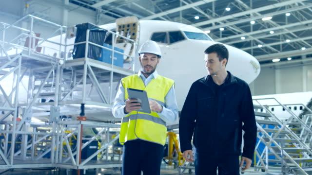항공기 정비 정비사와 수석 엔지니어는 큰 비행기 개발 시설을 통해 디지털 태블릿 컴퓨터 워크를 사용 합니다. 그들은 비행기를 분석, 검사, 개발 및 설계 합니다. - 항공 비행체 스톡 비디오 및 b-롤 화면