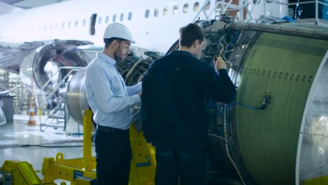 航空機整備士とチーフエンジニアは、格納庫内の飛行機のジェットエンジンを分析し、検査し、作業するために、デジタルタブレットコンピュータを使用しています。最適な機能性、作業、� - 機械工点の映像素材/bロール