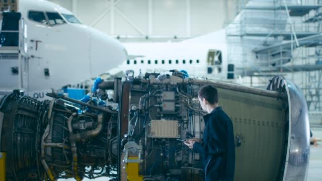 vídeos de stock, filmes e b-roll de o mecânico da manutenção dos aviões usa o computador da tabuleta de digitas para analisar, inspecionar e trabalhar no motor de jato do avião no hangar. otimizando o trabalho, a eficiência e o trabalho seguro da tecnologia - servidores
