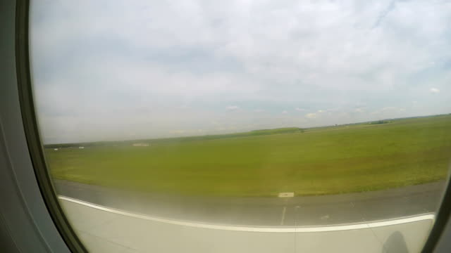 Aircraft taking off runway, gaining altitude in air, green landscape in window video