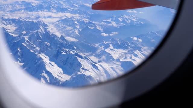 Bидео Aircraft window view of snow covered Alps mountains