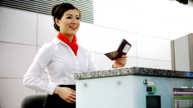 Airline check-in attendant handing passport to commuter 4k Airline check-in attendant handing passport to commuter at counter in airport terminal 4k anticipation stock videos & royalty-free footage