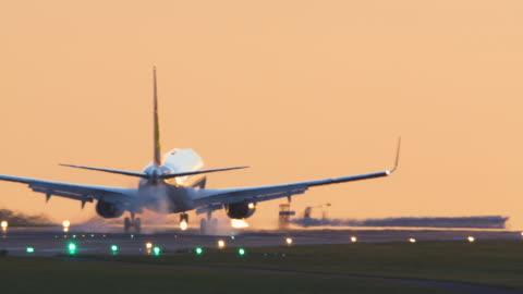 vidéos et rushes de avion de ligne venant se poser avec atterrissage au coucher du soleil. - avion