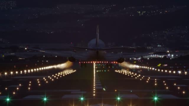 airliner landing on the runway at night - back view - lądować filmów i materiałów b-roll