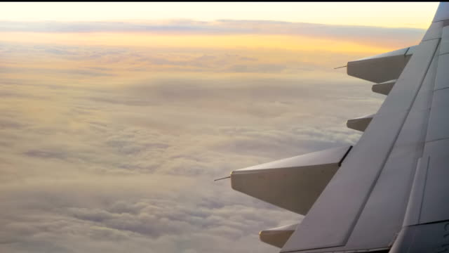 Airliner over the clouds in the rays of a beautiful sunset video