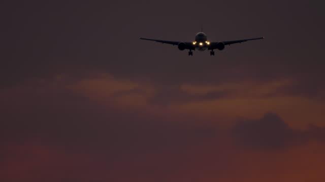flugzeug nähert sich bei sonnenuntergang bei sonnenuntergang - indochina stock-videos und b-roll-filmmaterial