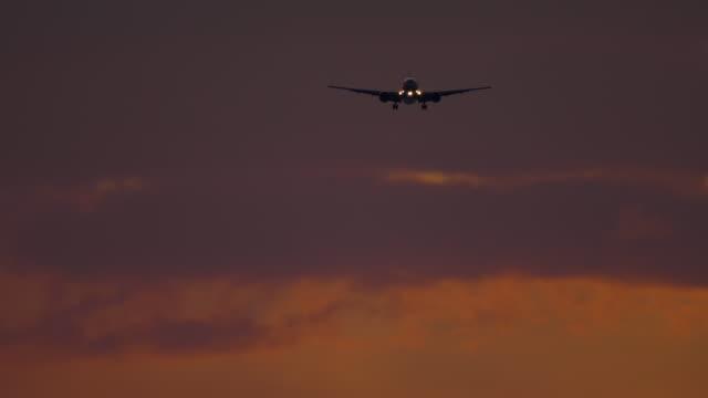 日没バックグラウンドで海の上に接近する飛行機 ビデオ