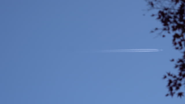 airplane contrail against clear blue sky video