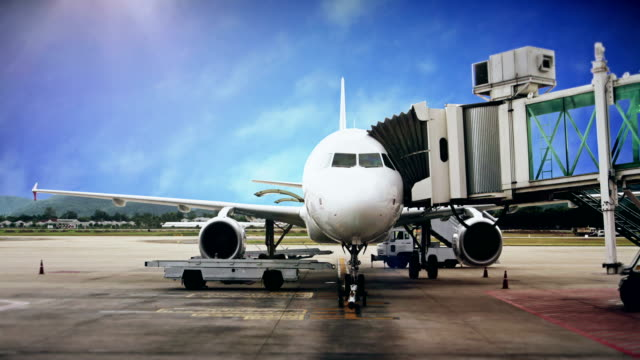 Airplane docks at the airport terminal boarding gate with against blue sky. Airplane docks at the airport terminal boarding gate with against blue sky. airfield stock videos & royalty-free footage