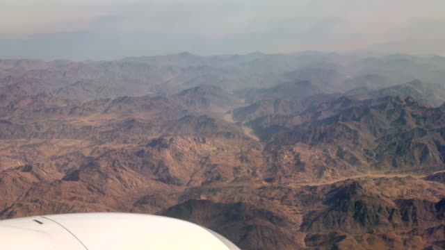 Airplane engine and desert mountains peaks