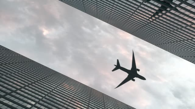 Airplane flies over office skyscrapers against a beautiful sky