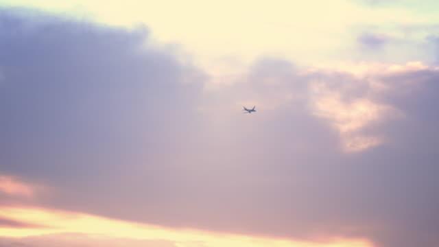 flygplan som flyger på en solnedgångs himmel - vidbild bildbanksvideor och videomaterial från bakom kulisserna