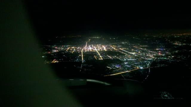 vidéos et rushes de avion survolant la ville pendant la nuit - aile d'avion