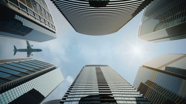 vidéos et rushes de avion volant au-dessus des gratte-ciel et se reflète dans les façades modernes en verre.  bâtiments corporatifs du centre-ville. - vue en contre plongée