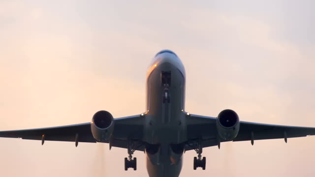 Airplane flying over summer sky in sunset, closeup, slow motion