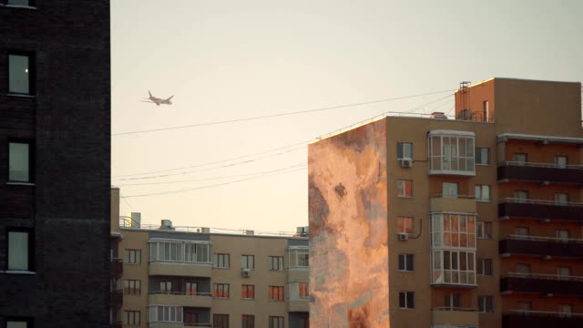 Airplane in a golden sky with modern buildings video