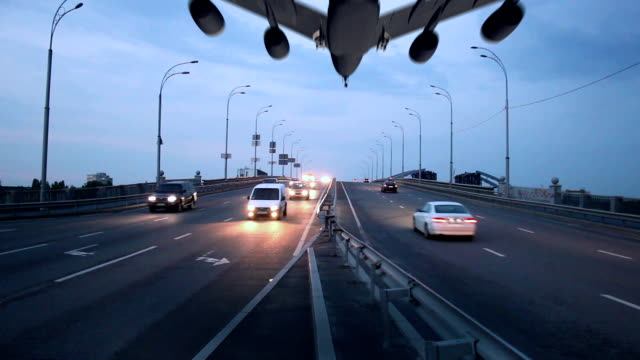 Airplane landing above city highway, transportation traffic dusk video