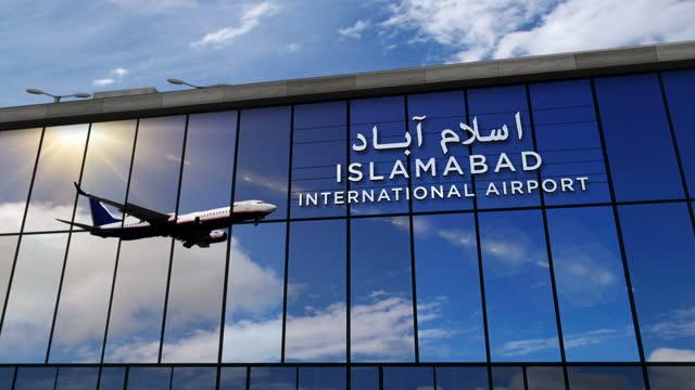 Airplane landing at Islamabad Pakistan airport mirrored in terminal