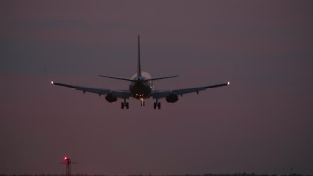 4k - airplane landing at night on airport runway - lądować filmów i materiałów b-roll