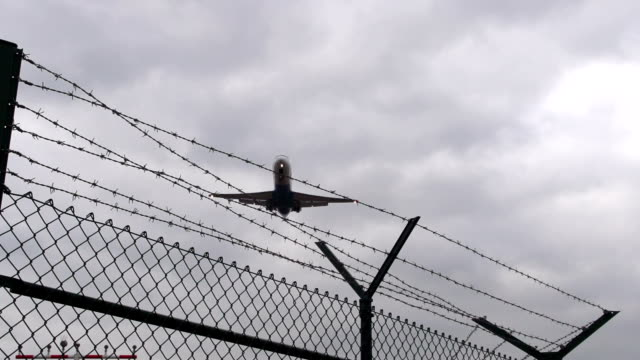 Airplane landing flies over barbed wire video