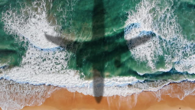vídeos de stock e filmes b-roll de airplane landing over the sea, aerial view top down shot, foamy ocean waves rolling and coming on a sand beach - ilha