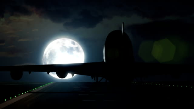 Airplane lands on airport runway in front of full moon video
