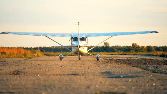 Airplane moving on a airfield, back view. Special plane goes on a runway to take off. propeller airplane stock videos & royalty-free footage