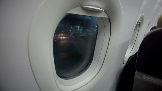 Avión de pasajeros mirando a través de la ventana de avión en el aeropuerto. De noche vuelo - vídeo