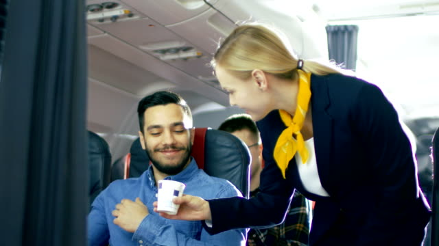 airplane stewardess/ flight attendant brings coffee for handsome hispanic male gentleman. they're inflight. business class of a commercial aviation interior is visible. - pasażer filmów i materiałów b-roll