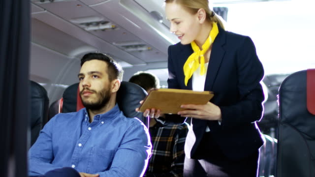 airplane stewardess/ flight attendant shows tablet computer with menu to hispanic male passenger. they're inflight. business class of a commercial aviation interior is visible. - kabina filmów i materiałów b-roll