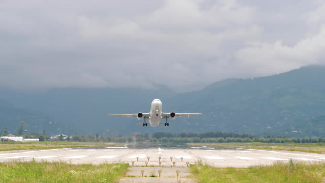 vídeos de stock e filmes b-roll de airplane takes off from the airport in mountains - georgia - remover