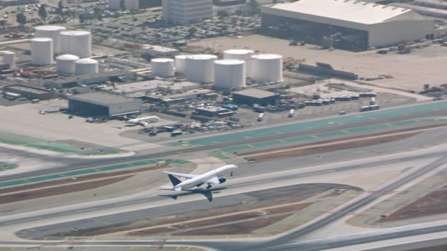 AERIAL Airplane taking off from the airstrip in CA Aerial shot of a commercial airplane taking off from the airstrip in an airport in California. Shot in USA. airport runway stock videos & royalty-free footage