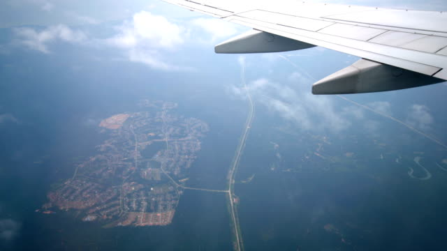 Airplane windows view flying above earth landscape and clouds video