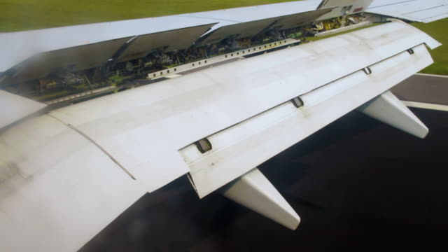 airplane wing during landing with flaps down on the sky over land - battere le ali video stock e b–roll