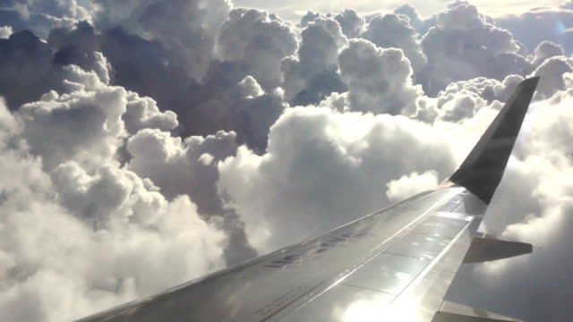 Airplane wing in cloudy sky - passenger view video