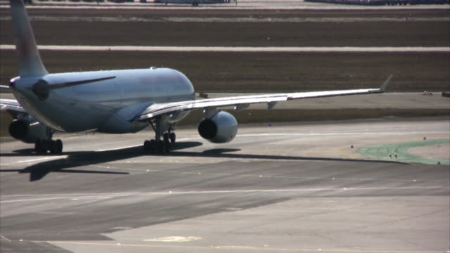 Airplanes on runway, waiting for lift off, airport tarmac (HD) video