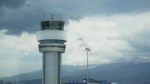 Airport Control Tower. Airport control tower at full capacity. Radar control tower with an airplane across the sky. Close up video