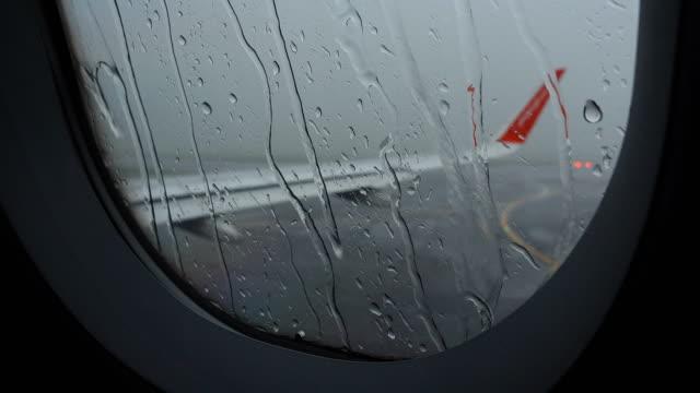 4k airport delay due to rain storm bad weather - skrzydło samolotu filmów i materiałów b-roll