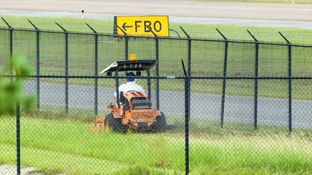 vídeos y material grabado en eventos de stock de aeropuerto hierba corte con cortacésped de montar en houston, texas, aeropuerto iah - valla límite
