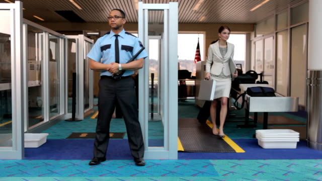Airport security guard stands watch at metal detector video